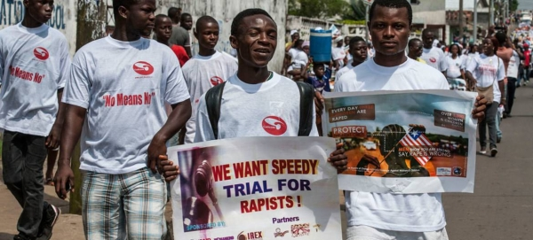 Liberian men march with anti-rape posters in this file picture. — Courtesy photo