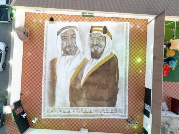 Ohud Abdullah Almalki, known as 'The Artist of the Nation', draws the largest coffee painting in the world using expired granules, illustrating seven renowned figures of Saudi Arabia and the neighboring United Arab Emirates.