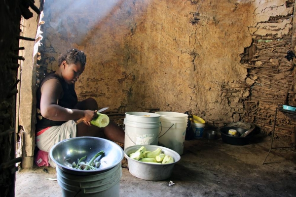 Osena Previlon's older daughter 14-year-old Bevalie Jean-Jacques, peels eggplants brought by her mother from the field as she helps with preparing lunch in the family's kitchen – a little mud house separated from the main house. — courtesy WFP/Alexis Masciarelli