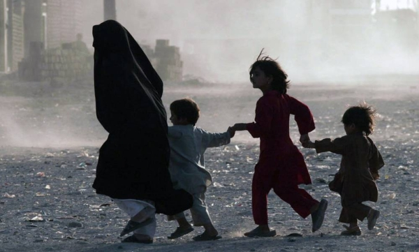 A family runs across a dusty street in Herat, Afghanistan. — courtesy UNAMA/Fraidoon Poya