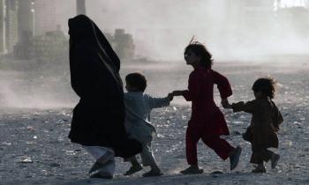 A family runs across a dusty street in Herat, Afghanistan. — courtesy UNAMA/Fraidoon Poya