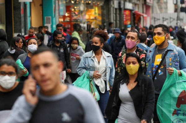 Brazilians take precautionary measures by wearing masks as they go about their business.