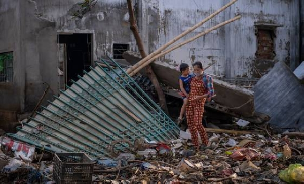 A woman carries her child as she walks past the ruins of a house destroyed by recent floods central Vietnam. — Courtesy photo