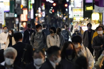 People wearing face masks walk in Tokyo's Shimbashi area amid the unabated rise in coronavirus infections in the capital. — courtesy Kyodo