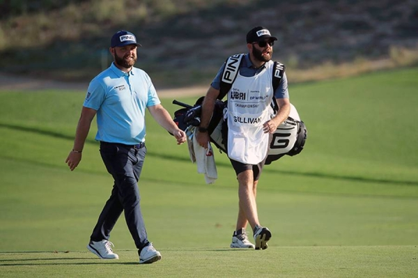 Andy Sullivan of England interacts with his caddie Thomas Riley  on the 18th hole during Day Three of the Golf in Dubai Championship at Jumeirah Golf Estates on Friday in Dubai, United Arab Emirates. (Photo by Andrew Redington/Getty Images)