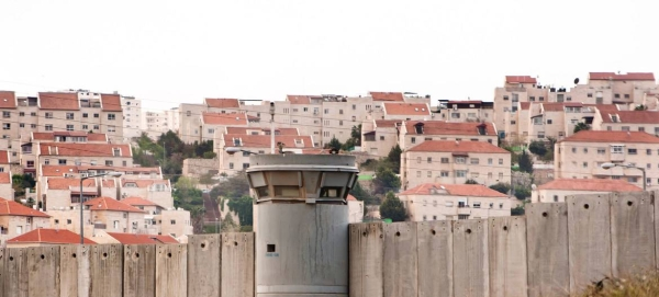 The Separation Wall in the occupied Palestinian Territory and behind it Israeli settlements are seen. — Courtesy photo