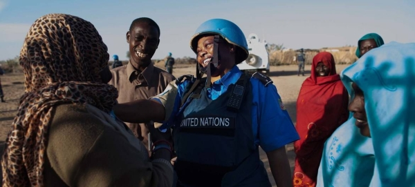 A UNAMID police officer interacts with women at a water point in Nifasha camp for internally displaced persons, north Darfur, in this file picture. — Courtesy photo