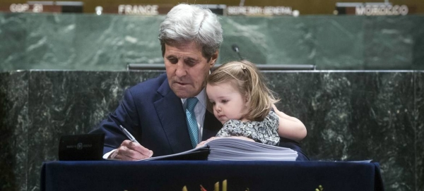 Former US Secretary of State John Kerry, accompanied by his grand-daughter, signs the Paris Agreement at UN headquarters in April 2016. — Courtesy photo