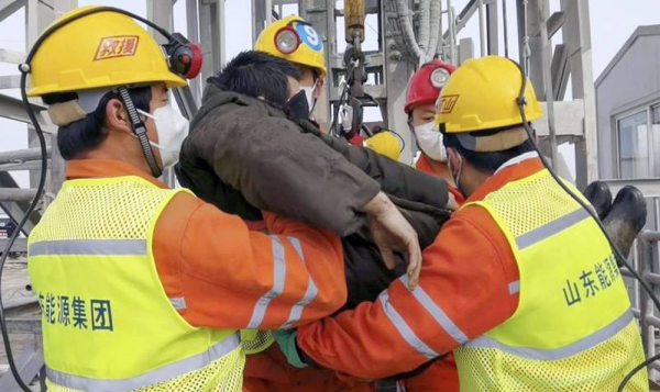 In this photo released by Xinhua News Agency, rescuers carry a miner who was trapped in a gold mine in Qixia City in east China's Shandong Province, Sunday.