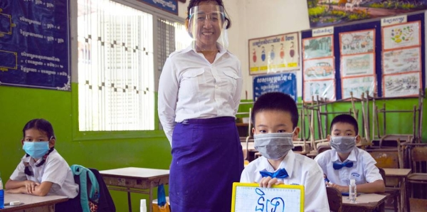 A teacher and her students practice COVID-19 school re-opening guidelines by wearing face masks and maintaining physical distance at a primary school in Phnom Penh, Cambodia. — courtesy UNICEF/Seng