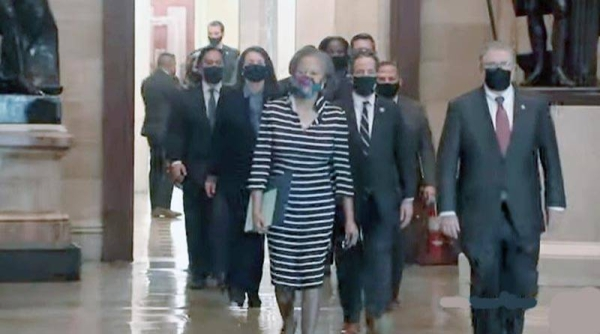 A TV grab shows the impeachment managers wearing black masks and walking two-by-two through the very halls where rioters had overtaken the Capitol earlier this month in a deadly siege, being led into the Senate chamber by the lead impeachment manager, Rep. Jamie Raskin of Maryland, who read the article of impeachment.