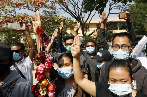 Supporters show the three-finger salute of protest while arrested activist male a court appearance in Mandalay, Myanmar on Friday. Huundred of students and teachers have taken to the streets to demand the military hand power back to the elected politicians.