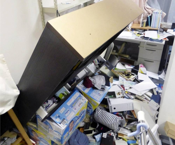 A bookshelf is seen tipped over at a home in Koriyama, Fukushima Prefecture, late Saturday after a powerful earthquake struck the region. — courtesy Kyodo