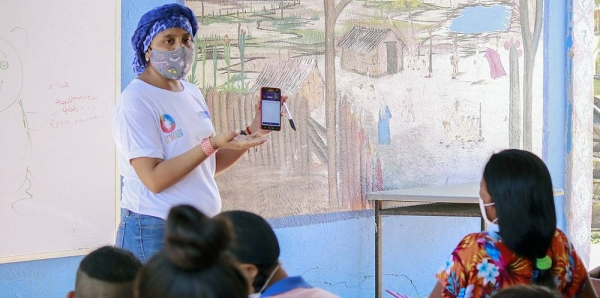 A teacher explains how to use the application that will allow students to access educational material. — courtesy El Origen Foundation