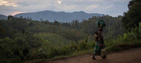 A woman, carrying her child, walks back to her home from the fields in D.R. Congo's restive North Kivu province in this courtesy file photo.
