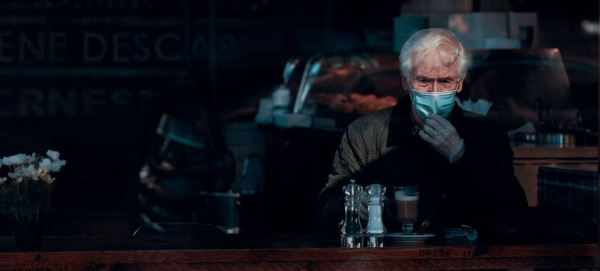 A man wears a face mask and gloves while sitting in a cafe in Glasgow, Scotland. — Courtesy photo