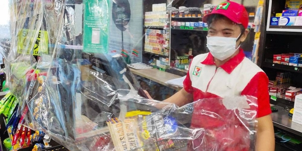 A convenience store requires staff to wear a mask, observe physical distance, and use a plastic sheet barrier as safety measures to prevent the spread of COVID-19, Muntinlupa City, Philippines. — courtesy ILO/Minette Rimando