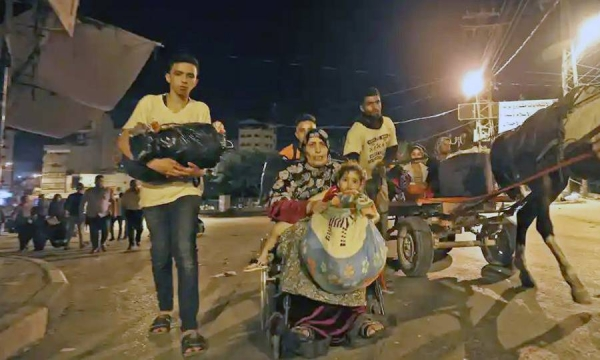 Palestinians in Gaza seen fleeing their homes Thursday night to take refuge in UNRWA schools. — courtesy Twitter