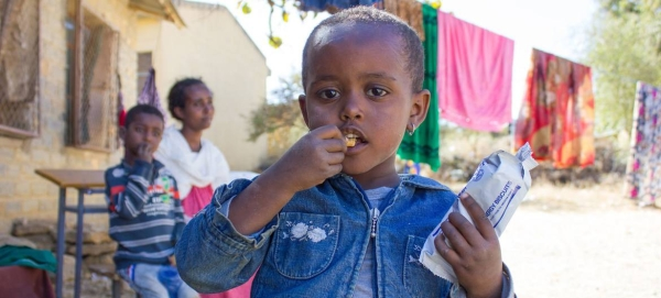 A three-year-old girl in western Tigray eats a high-energy biscuit to boost her nutrition levels. — Courtesy file photo