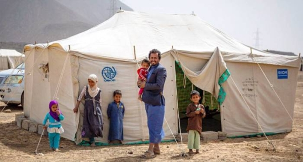 File photo shows a father standing with his children outside their tent in a displacement site outside Marib City, Yemen. — courtesy IOM/Olivia Headon