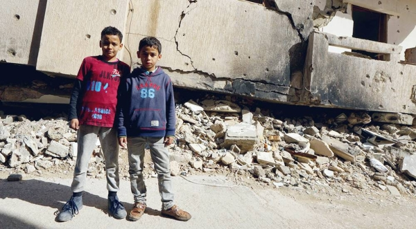 File photo shows young boys standing in front of a destroyed building in Benghazi Old Town in Libya. — courtesy UNOCHA/Giles Clarke