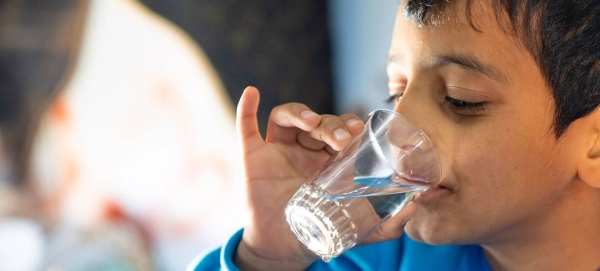 A young boy drinks a glass of water from a new water network connected to the Za'atari Refugee Camp in Jordan. — Courtesy file photo