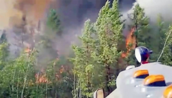Volunteers and firefighters battle to control the wildfire in the clearing of a Siberian forest.