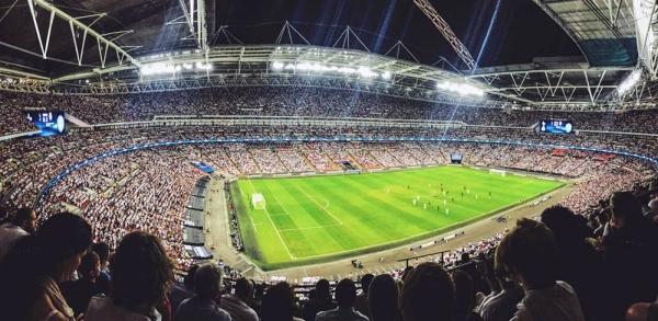 A crowd watching a football game inside Wembley Stadium in England. (September 2016) — courtesy Unsplash/Mitch Rosen