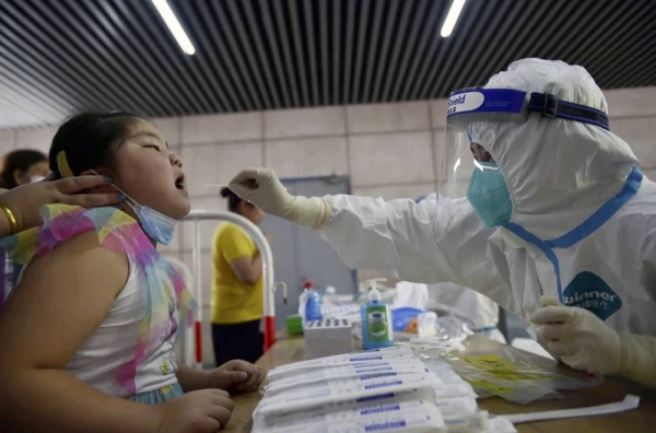 A nurse takes a throat swab in a new round of coronavirus testing in Nanjing, China. — courtesy Chinatopix