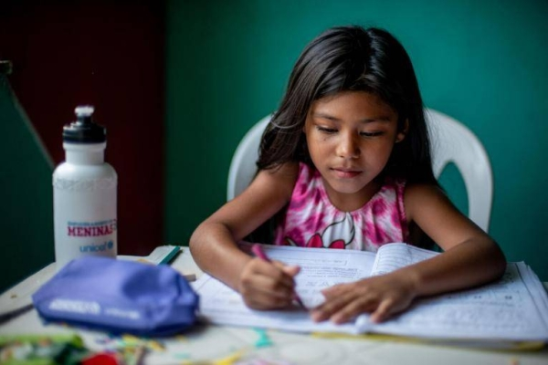 Ágata Melo, 8, does school activities at her home in Vigia, in the northern Brazilian state of Pará, in the Amazon region.