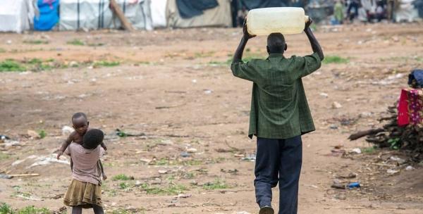 A man carries water close to Bujumbura in Burundi. — courtesy UNICEF/Karel Prinsloo