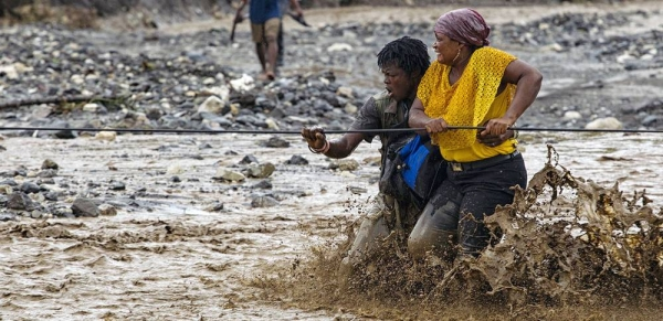People cross a flooded river in western Haiti after a bridge was washed away by Hurricane Matthew. (file) — courtesy MINUSTAH/Logan Abassi