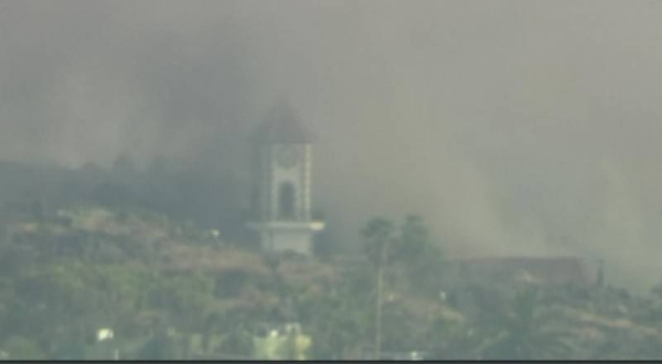 A cloud of dense smoke engulfs the bell tower of the church on La Palma before it collapsed.