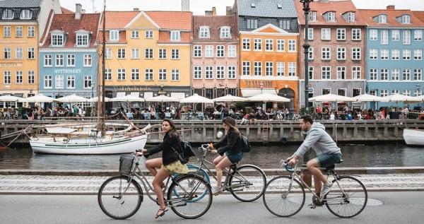 Tourists biking at Nyhavn in Copenhagen, Denmark. — courtesy Unsplash/Febiyan